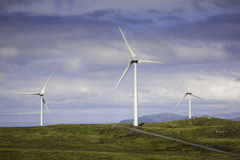 Modern windmills on a green hill. Wind turbines. Norway. Vagsøy Royalty Free Stock Image