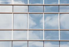 Modern windows. Windows from a modern building with the reflection of the sky and clouds Royalty Free Stock Photos