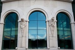 Modern windows with statues. With reflection stock photography