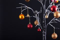 Modern winter Christmas tree. Modern Christmas tree with bare snow covered branches, decorated with hanging glitter balls, all on a black background Royalty Free Stock Image