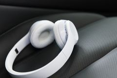Wireless headphones on the car seat. Modern wireless internet technology concept: macro view of the white wireless headphones on the black leather car seat with royalty free stock photography