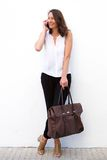 Modern woman with bag using mobile phone Stock Photography
