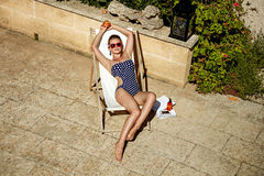 Modern woman in beachwear in lounger with peach relaxing Royalty Free Stock Images