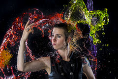Modern Woman Being Splashed with Colorful Water Stock Image