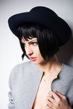 Modern woman with black hat on gray Royalty Free Stock Photos