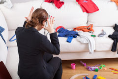 Modern woman can't stand a house mess. Young active woman can't stand a big mess what she has seen at home Stock Image