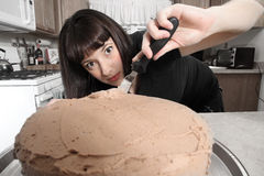 Modern woman frosting cake Royalty Free Stock Photo