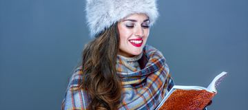 Modern woman in fur hat isolated on cold blue reading book. Winter things. Portrait of happy modern woman in fur hat isolated on cold blue reading book Royalty Free Stock Images