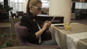 Modern woman in glasses using mobile phone on background interior luxury cafe. Beautiful woman typing message on smartphone during business lunch in modern stock video