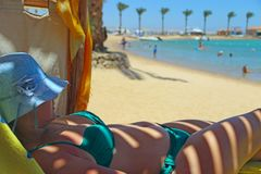 Modern woman laying on chaise-longue in shadow of umbrella enjoying vacation stock images