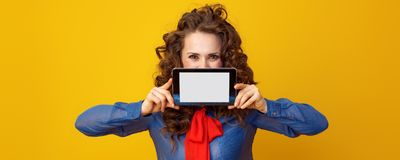 Woman on yellow background hiding behind tablet PC blank screen. Modern woman with long wavy brunette hair hiding behind tablet PC blank screen on yellow royalty free stock photos