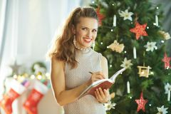 Modern woman near Christmas tree writing in notebook stock images