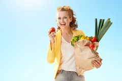 Modern woman with paper bag with groceries biting apple ag. Happy modern woman in yellow jacket with paper bag with groceries biting an apple against blue sky stock photography