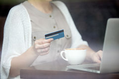 Modern woman paying online with credit card. Shot through window Stock Images