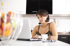 Modern woman reading e-mails at her breakfast Royalty Free Stock Photography