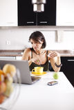 Modern woman reading e-mails at her breakfast Royalty Free Stock Image