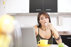 Modern woman reading e-mails at her breakfast Stock Photo