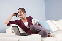 Modern woman relaxed on couch with phone, laptop stock photos