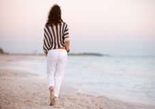 Modern woman on seacoast at sunset walking. Seen from behind modern woman in white pants and striped shirt on the seacoast at sunset walking stock photography