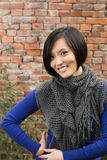 Modern woman smile. Modern woman of Asian smile against old brick wall Royalty Free Stock Photo