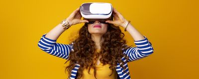 Modern woman in striped jacket on yellow background in VR gear Stock Image
