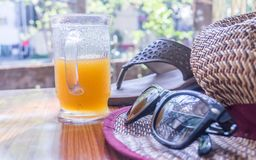 Modern women essential accessories for sunday weekend activities on wooden table. Sunglasses placed over Straw hat, flip flops, royalty free stock images