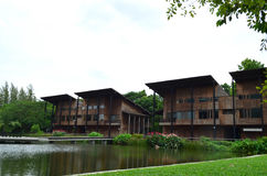 Modern wood building  behind pond and lawn Royalty Free Stock Photos