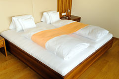 Modern wooden bed in hotel. Modern wooden double bed shot in hotel Stock Photo
