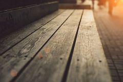 Modern wooden bench with deep texture close up. At sunset warm light stock image