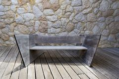 Modern wooden bench. Modern designed wooden outdoor bench on wooden patio with quarrystone wall in back Royalty Free Stock Photos