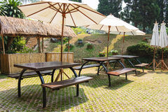 Modern wooden bench and umbrella in Thailand park Royalty Free Stock Images