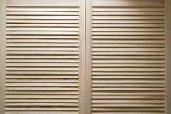 Modern wooden cabinet with strips in classic rustic style. Wardrobe closet with shutter plank doors.  royalty free stock images