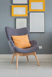Modern wooden chair with orange pillow Royalty Free Stock Images