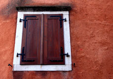A modern wooden dark brown closed window with white frame on a r Royalty Free Stock Photography