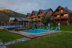 Modern wooden hotel mountains waterpool dusk Stock Images