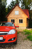 Modern wooden house and car. Modern wooden Russian traditional house and the car of the red colour stock photo