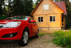 Modern wooden house and the red car. Modern wooden Russian traditional house and the car of the red colour stock image