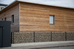 Modern wooden house with stone fence in front Royalty Free Stock Image