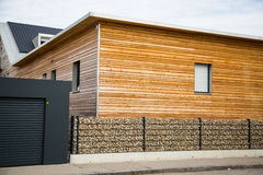 Modern wooden house with stone fence in front Stock Photos