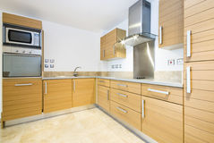 Modern wooden kitchen. With silver appliances Royalty Free Stock Photos