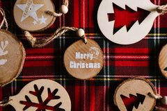 Modern wooden ornaments with a Christmas message for decoration, on a red tartan background. Christmas background stock photos