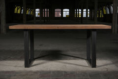 Modern wooden table in the loft interior Stock Photography
