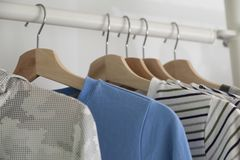 Modern wooden wardrobe with clothes hanging on rail. In walk in closet design interior stock image