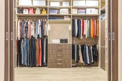 Modern wooden wardrobe with clothes hanging on rail in walk in closet. Design interior stock photo