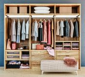 Modern wooden wardrobe with clothes hanging on rail in walk in closet design interior stock images