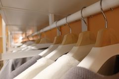 Modern wooden wardrobe with clothes hanging on rail in walk in closet, stock photos