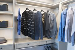 Modern wooden wardrobe with clothes hanging on rail in walk in closet. Design interior stock photos
