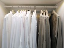 Modern wooden wardrobe with mens clothes hanging on rail in walk in closet, in scandinavian style. stock photography