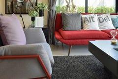 Modern woonkamerontwerp met hoofdkussens op de rode bank en het decor Stock Afbeeldingen