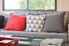 Modern woonkamerontwerp met rode en grijze hoofdkussens op bank Stock Foto's